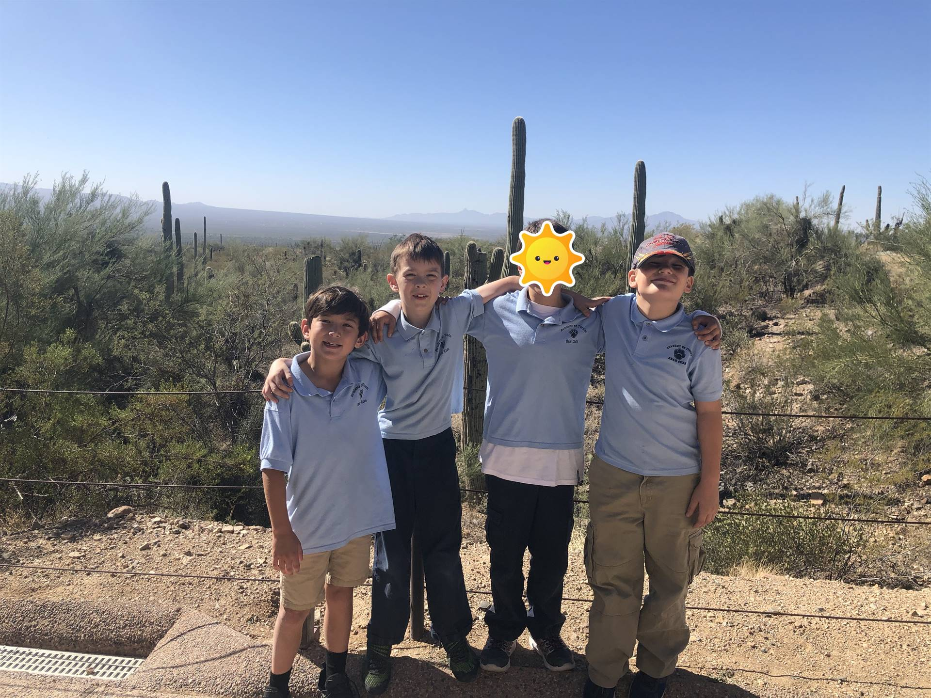 students pose in front of desert landscape