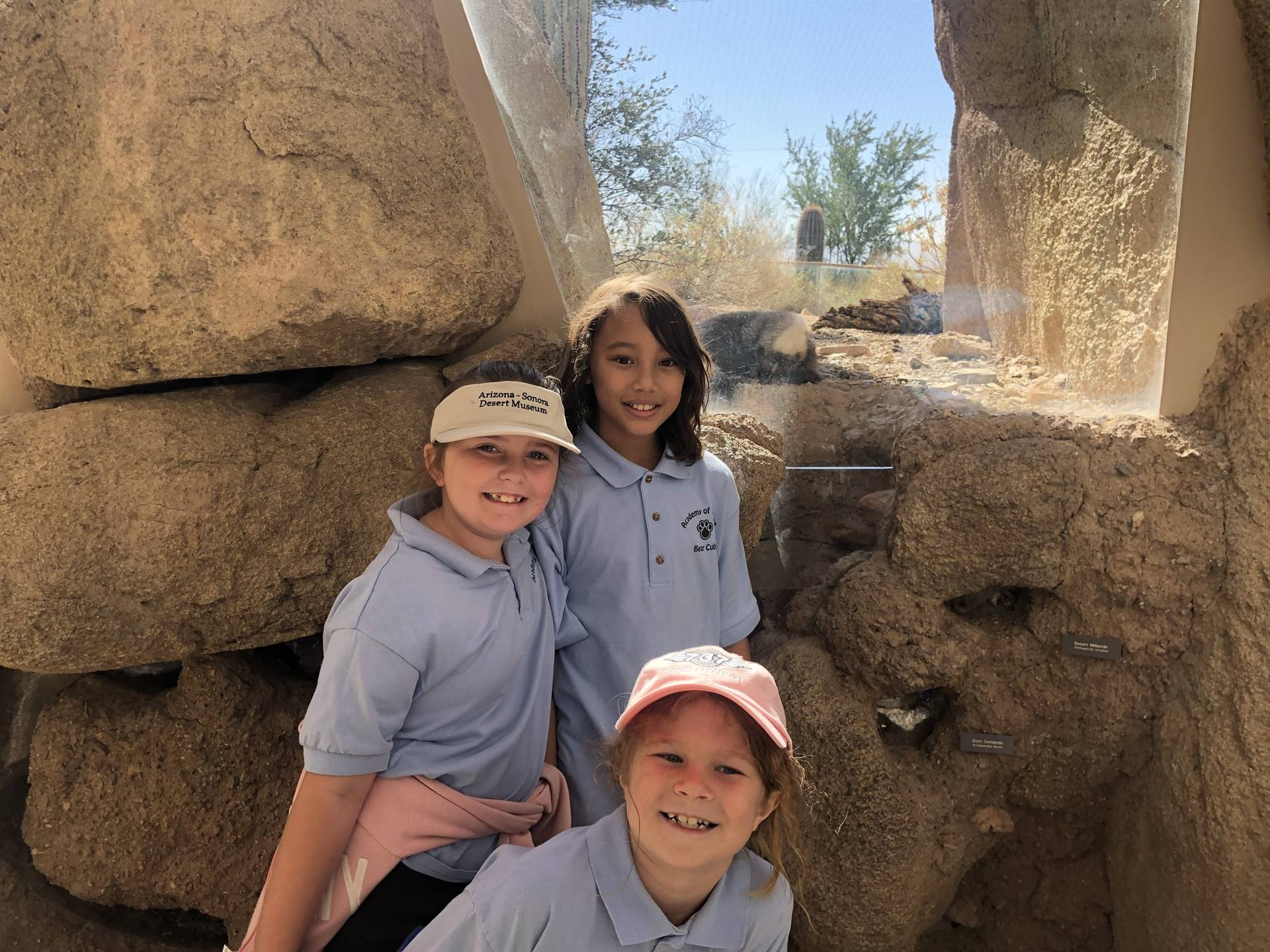 3 students near the prairie dog exhibit