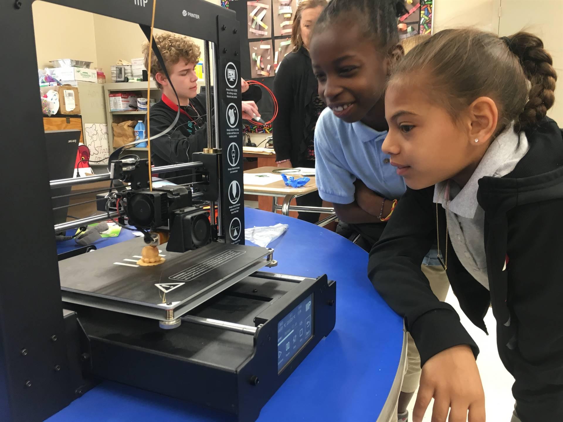 students look at 3d printer